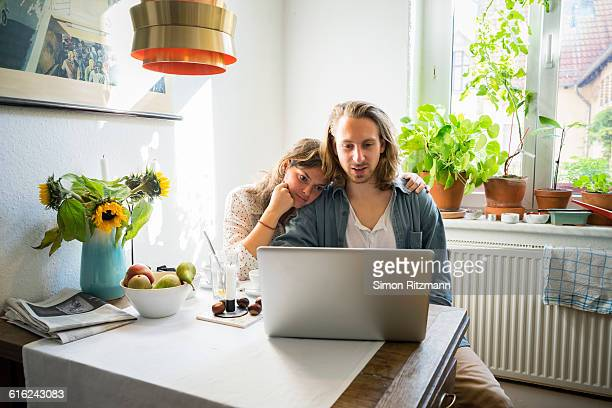 young couple using laptop in kitchen - heteroseksueel koppel stockfoto's en -beelden