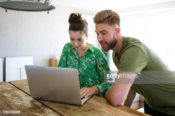 ungt par som använder laptop tillsammans hemma - endast vuxna bildbanksfoton och bilder