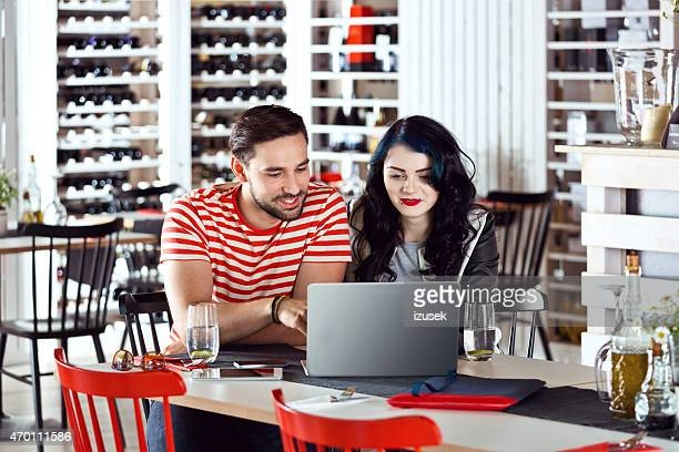 young couple using laptop together in the wine bar - free business coaching stock pictures, royalty-free photos & images