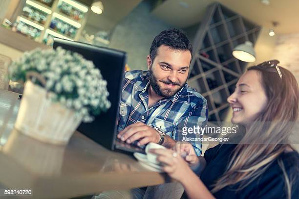 Young Couple using Laptop while Drinking Coffee at Restaurant