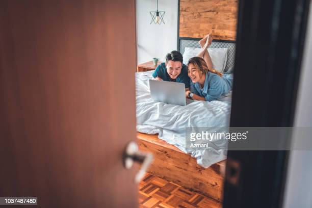 young couple using laptop while lying on bed - ajar stock pictures, royalty-free photos & images