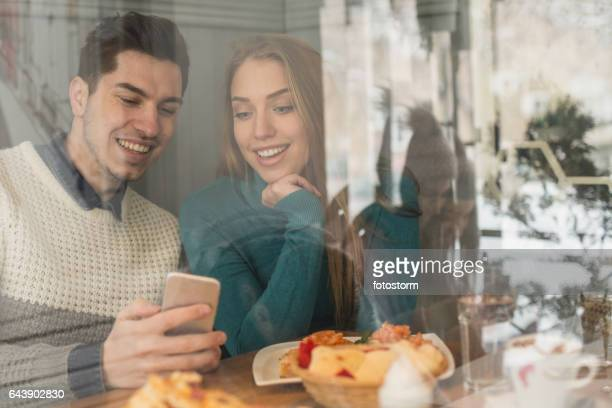 Young couple using mobile phone in cafe