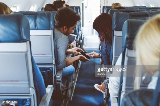Jong koppel gebruik mobiele telefoon in de vlucht
