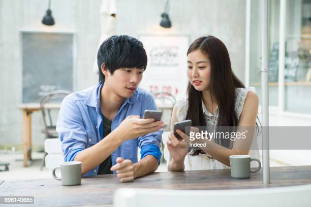 Young couple using smart phone at cafe