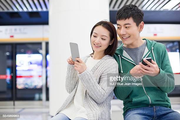 Young couple using smart phone at subway station