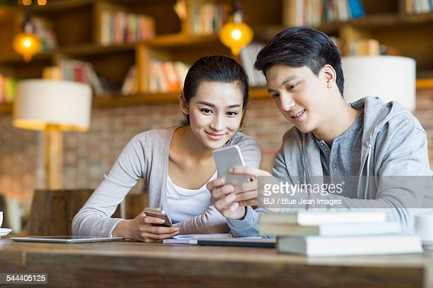 Young couple using smart phone in cafe