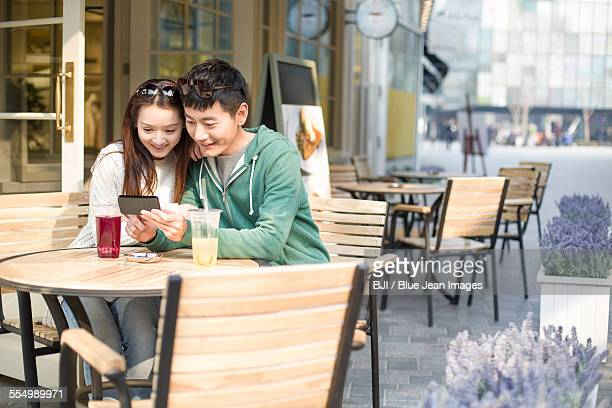 Young couple using smart phone in restaurant