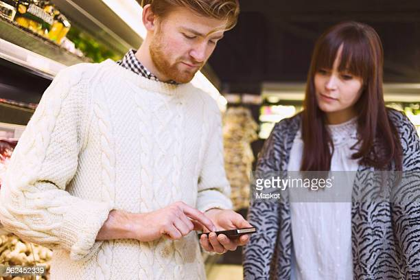 Young couple using smart phone in supermarket