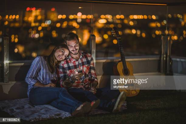 Young couple using smart phone on a penthouse terrace by night.
