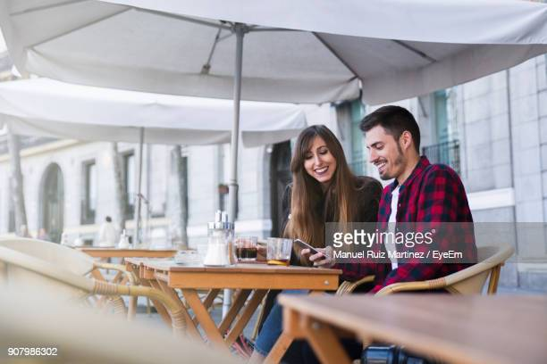 Young Couple Using Smart Phones While Sitting On Sidewalk Cafe
