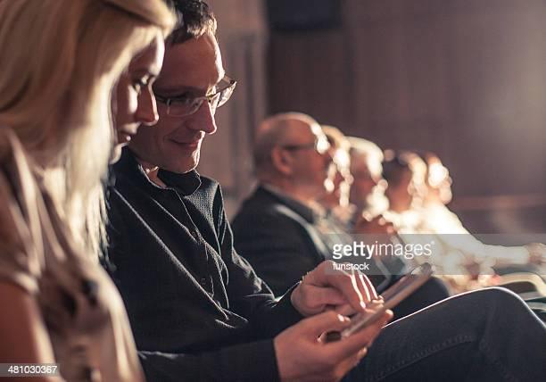 young couple using smartphone between theatre show - entertainment evenement stockfoto's en -beelden