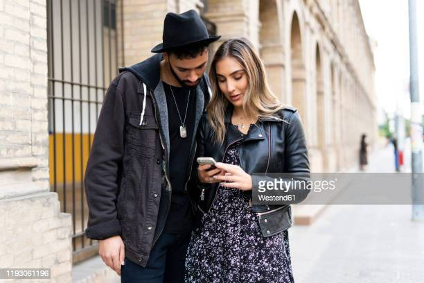 young couple using smartphone in the city - side by side stock pictures, royalty-free photos & images