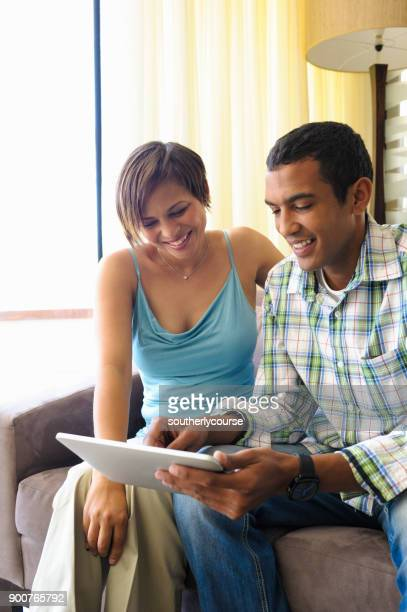 young couple using tablet computer - indian cleavage stock pictures, royalty-free photos & images