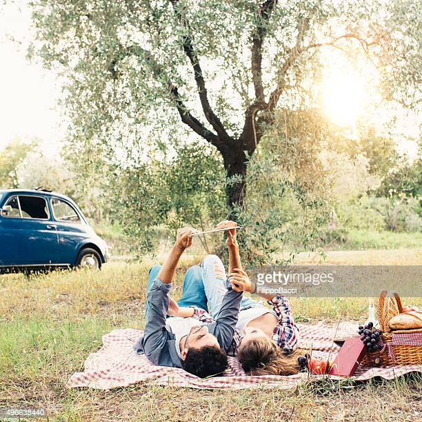 Young Couple Using Tablet During Picnic Outdoor