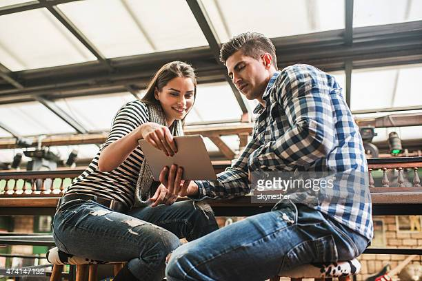 young couple using touchpad together in a cafe. - elektronische organiser stockfoto's en -beelden