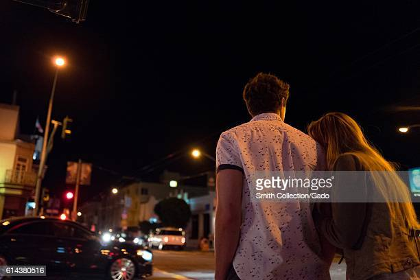A young couple viewed from behind walks down a street with the woman holding the man's arm and leaning her head affectionately on his shoulder in the...