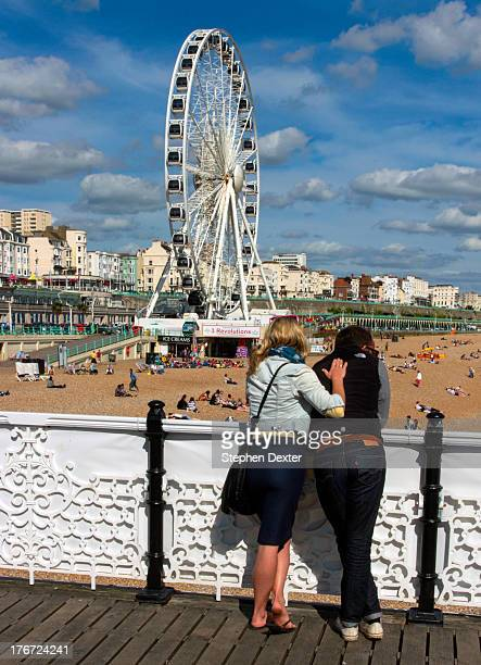 CONTENT] Young couple viewing Brighton seafront from the pier A sunny day with clouds in the sky