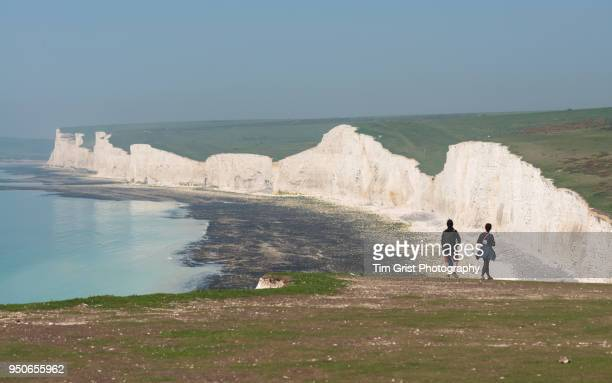 young couple viewing the seven sisters cliffs - seven sisters cliffs stock photos and pictures