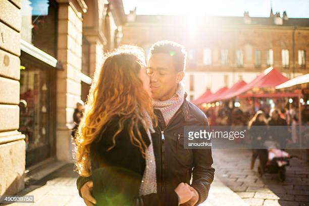 young couple visiting christmas market in milan - black women kissing white men stock pictures, royalty-free photos & images