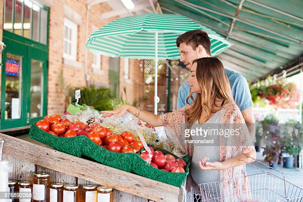 Young couple waiting a baby making grocery at farmer market