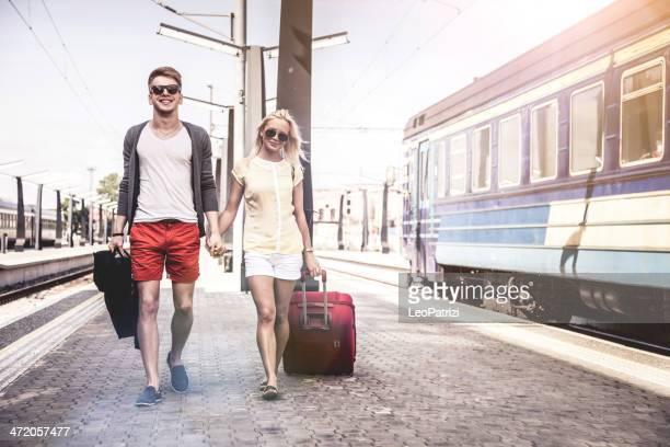 Jeune couple attend un train sur la plate-forme