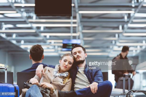 Young couple waiting for flight and sleeping
