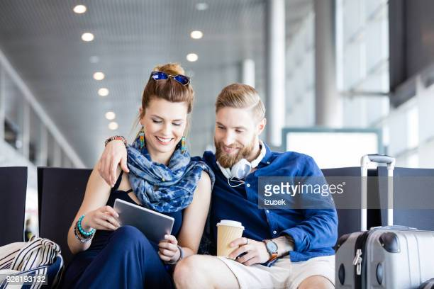 young couple waiting for flight in airport lounge - izusek imagens e fotografias de stock