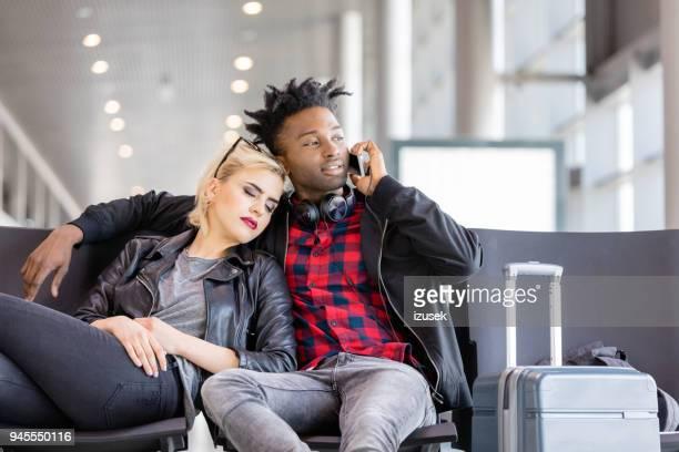 giovane coppia in attesa di volo in aeroporto internazionale - izusek foto e immagini stock