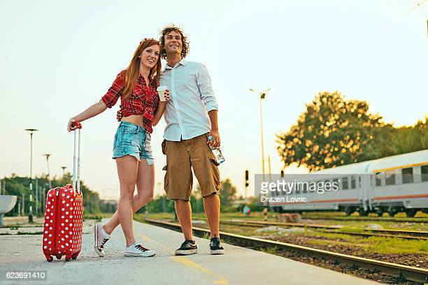 Young couple waiting for train and expressing happiness