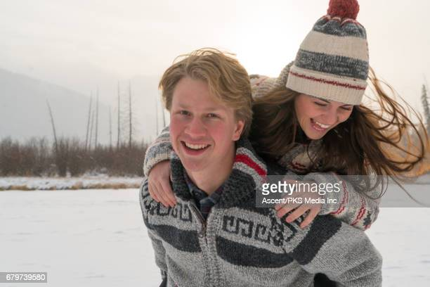 Young couple walk across frozen lake, snowy mountain setting