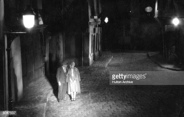 Young couple walk along a lamplit Parisian street in a scene from the film 'Sous les Toits de Paris' , directed by Rene Clair.
