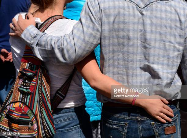 Young couple walk with arms around each other in Santa Fe, New Mexico.