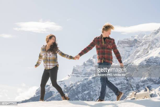 Young couple walk with dog, in snowy mountain setting