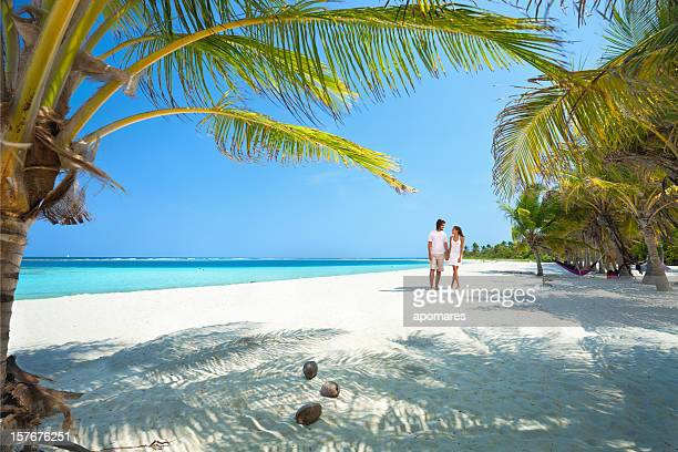 young couple walking along a lonely tropical island beach - caribbean sea stock pictures, royalty-free photos & images
