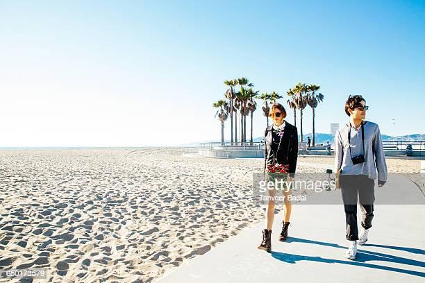 Young couple walking along beach walkway