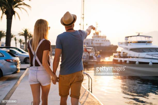 young couple walking along harbor holding hands - marina stock photos and pictures