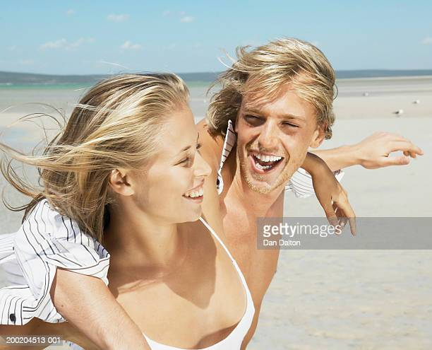 Young couple walking arm in arm along beach, laughing, close-up
