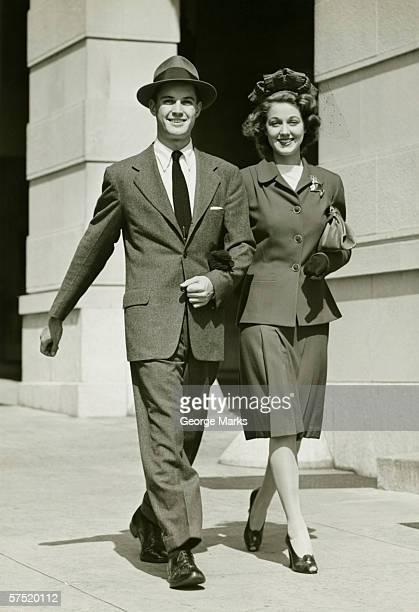 Young couple walking arm in arm on sidewalk, (B&W)