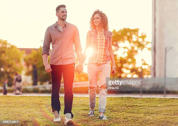 Young couple walking at sunset.