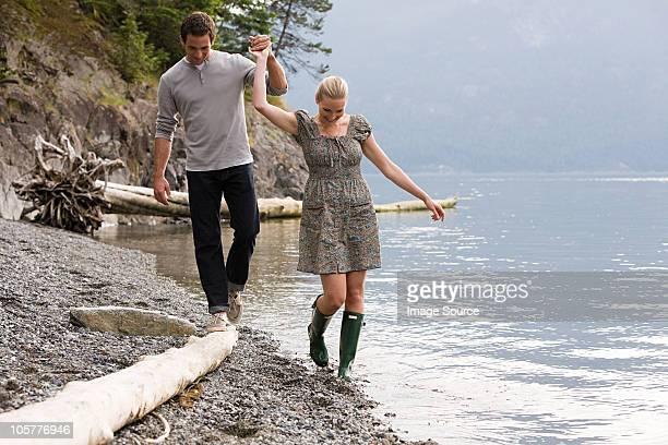Junges Paar zu Fuß durch den lake Hände halten