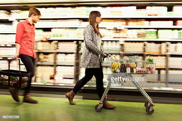 Young couple walking by shelves at supermarket