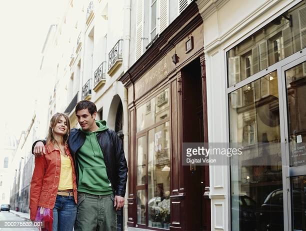 Young couple walking by shops in street