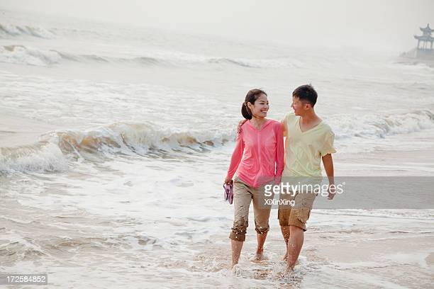 Young couple walking by the waters edge on the beach, China