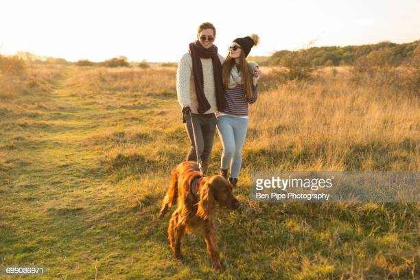 Young couple walking dog in field
