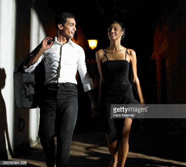 young couple walking down street at night - hans neleman ストックフォトと画像