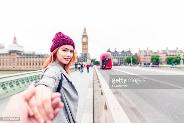Jong koppel lopen hand in hand over Westminster Bridge naar Big Ben en het parlementsgebouw.