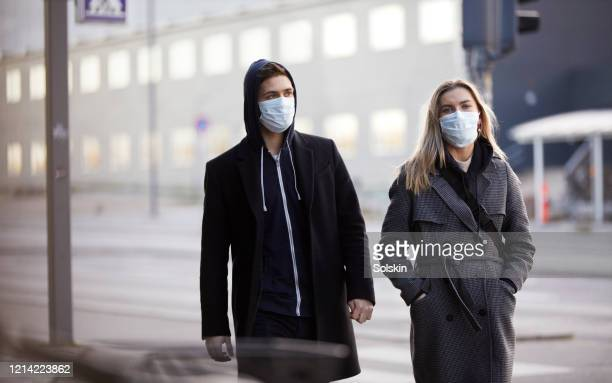 young couple walking in city, wearing protective face masks - relationship stockfoto's en -beelden