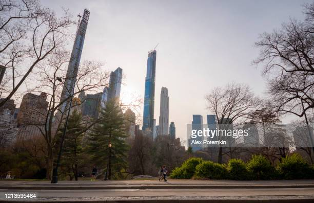 young couple walking in front of manhattan skyline on central park deserted because of coronavirus outbreak. - alex potemkin coronavirus stock pictures, royalty-free photos & images