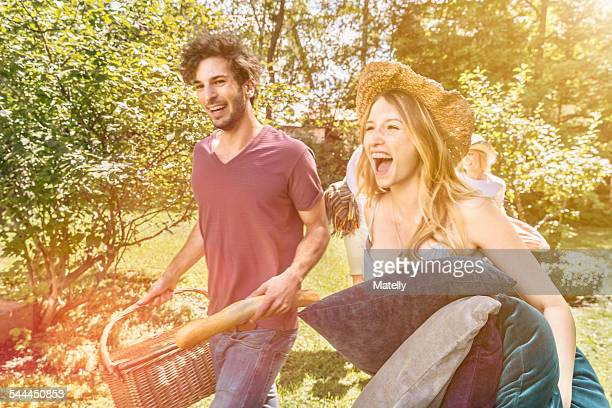 Young couple walking in garden preparing for picnic