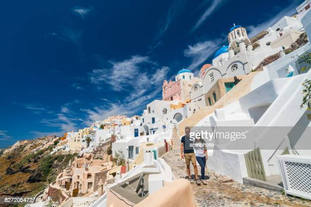young couple walking in oia santorini